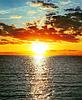Czerwony zachód słońca nad wodą z falami | Stock Foto