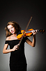 Woman performer with violin in darkness | Stock Foto