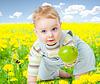 Baby unter Löwenzahn mit gesunden Lebensmitteln Apfel | Stock Foto