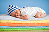 다채로운 수건 스택에 신생아 잠자는 아기 | Stock Foto