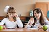 Две девочки, сидя за партой во время урока | Фото