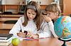 Dwie dziewczyny posiedzenia w szkole biurko z telefonem komórkowym | Stock Foto