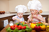 Zwei kleine Mädchen Zubereitung von gesundem Essen auf Küchenpapier | Stock Foto
