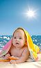 바다 해변에서 다채로운 수건에 사랑스러운 아기 | Stock Foto