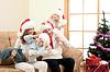 Счастливая семья в новогодних шапках на диване | Фото