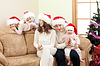 Szczęśliwa rodzina w Boże Narodzenie Santa `s kapelusze na kanapie | Stock Foto