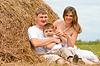 Счастливая семья имеет удовольствие в стоге сена вместе | Фото