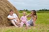 幸福的家庭在干草堆或草垛西瓜 | 免版税照片
