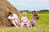 Счастливая семья сидит возле стога сена | Фото