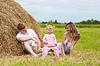 Happy family sitting near haystack | Stock Foto