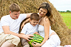 Happy family in haystack or hayrick with watermelon | Stock Foto