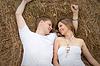 Glückliches junges Paar liegt auf Heuhaufen | Stock Foto