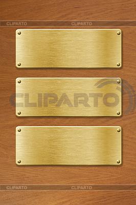 Drei goldene Metallplatten über Holzstruktur | Foto mit hoher Auflösung |ID 3658402