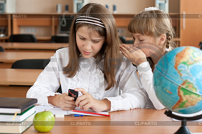 Dwie dziewczyny posiedzenia w szkole biurko z telefonem komórkowym | Foto stockowe wysokiej rozdzielczości |ID 3659099