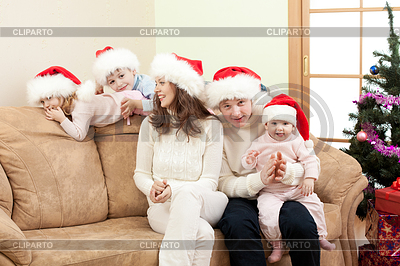 Glückliche Familie in Christmas Santa `s Hut auf dem Sofa im | Foto mit hoher Auflösung |ID 3660306